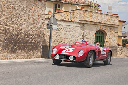 drivers on a vintage competition car Ferrari 500 TR spider Scaglietti  1956  passes through a Tuscan village in historical rally Mille Miglia, on May 17, 2014 in Colle di Val d Elsa, Tuscany, Italy