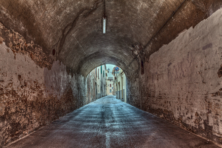 urban decline: dark narrow underpass in the old town - urban decay, grunge alley in Italy