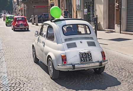 vintage Fiat 500 with a green balloon in a line of the old italian mini car, during the rally  Emozioni 500   on June 8, 2014 in Forli , Italy