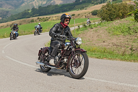 biker rides an old italian motorcycle Moto Guzzi of the thirties, at rally  IX Moto Guzzi Memorial Zigolo  on July 13, 2014 in Meldola, FC, Italy