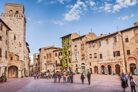 people walking in the lively square  Piazzza della Cisterna  with the medieval  devil s tower , the ancient palaces and the well of the water cistern, on May 17, 2014 in San Gimignano Tuscany  Italy