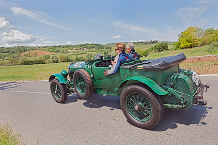 the crew Grossmann - Rose on a classic car Bentley 6 1 2 litre Tourer  1927  travel in the country of Tuscany during the race Mille Miglia, on May 17, 2014 in Colle di Val d Elsa, Tuscany, Italy
