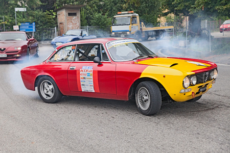 swerve: driver drifting with smoking tires on a vintage racing car Alfa romeo GTV 2000 in  in rally 3� Raduno auto e moto d epoca di Villafranca  on July 27, 2014 in Forli , Italy