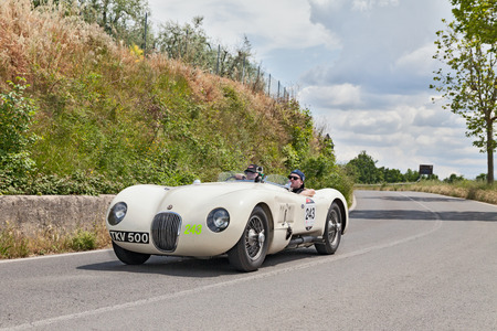 miles: the crew Hans-Martin and Mahnaz Schneeberger on a vintage racing car Jaguar C-Type  1952  travel in the country of Tuscany during the historical race Mille Miglia, on May 17, 2014 in Colle di Val d Elsa, Tuscany, Italy Editorial