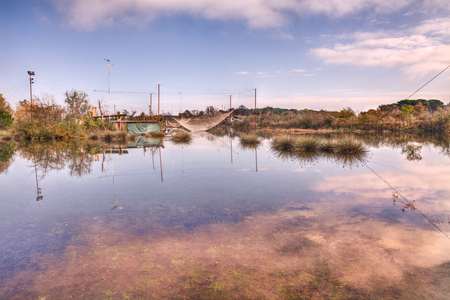 morass: landscape of the swamp with reeds and rushes in a wetland near Ravenna, Italy, and fishing huts with net on the lagoon