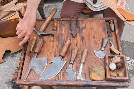 work table with old tools of the artisan shoemaker for cutting and sewing the leather - reenactment of ancient medieval work