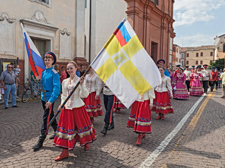 cossack parade: street parade of the folk dancers Cossack song and dance ensemble Volnaya Step from Stavropol, Russia, with national and city flag, during the International Folklore Festival of Russi, on August 3, 2014 in Russi, RA, Italy