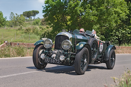 the crew W. Schreiber B. Ostman on a vintage racing car Bentley 4.5 Litre S.C. (1930) travels in Tuscany during the italian historical race Mille Miglia, on May 17, 2014 in Colle di Val dElsa, Tuscany, Italy