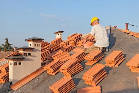 techos: trabajador de la construcción en un techo que lo cubre con tejas - renovación del techo: instalación de papel de alquitrán, nuevos azulejos y la chimenea Foto de archivo