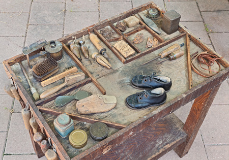 work table: work table with small shoes for children and old tools of the artisan shoemaker for repair and finishing shoe