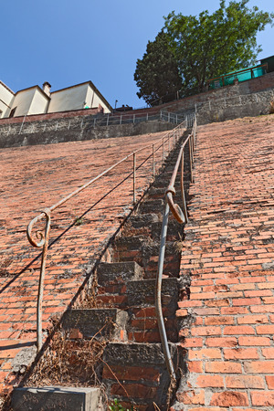 inclined: very steep staircase, dangerous climb on a high inclined brick wall Stock Photo