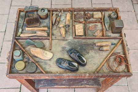 work table with small shoes for children and old tools of the artisan shoemaker for repair and finishing shoe