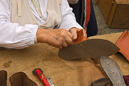 made by hand: elderly shoemaker in antique costume making medieval shoes at -Fiera di San Rocco- on November 7, 2010 in Faenza, RA, Italy. Fair of San Rocco hosts historic re-enactments, shows and market