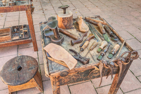 old shoes: work table with old tools of the artisan shoemaker to cut and shape the leather to make shoes