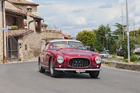 farina: the crew D. Parmegiani - M. Bonzi on a rare vintage sports car Ferrari 250 GT Europa Pinin Farina (1955) in Tuscan village during the historic race Mille Miglia, on May 17, 2014 in Colle di Val d Elsa, Tuscany, Italy Editorial