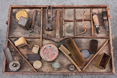 bygone: work table with old tools of the artisan shoemaker for repair, cleaning, polishing and finishing shoes
