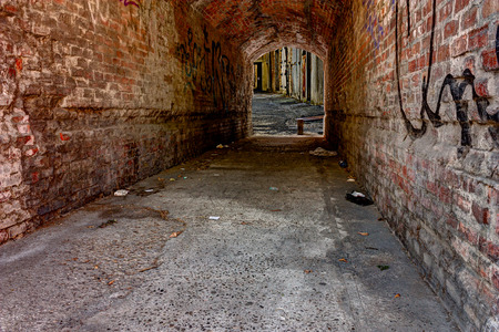 filthiness: dirty underpass in the old town  - dark, narrow grunge alley in the ghetto - squalid old passage in the slums of the city Stock Photo