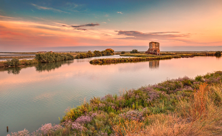comacchio: landscape at sunset of the swamp with ruins of an old house - the lagoon in the natural reserve of Comacchio, Ferrara, Italy