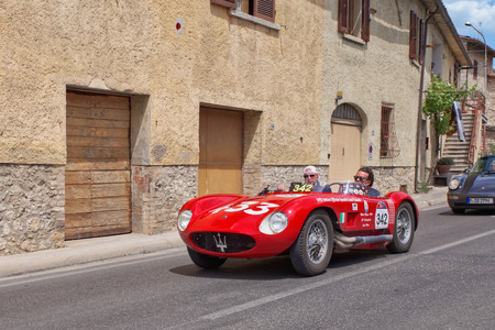 s and m: COLLE VAL D ELSA, SI, ITALY - MAY 17: the drivers P.Berton M. Peruzzi on racing car Maserati 150 S (1955) travels in Tuscany during the historic classic car race Mille Miglia, on May 17, 2014 in Colle Val d Elsa, Siena, Italy