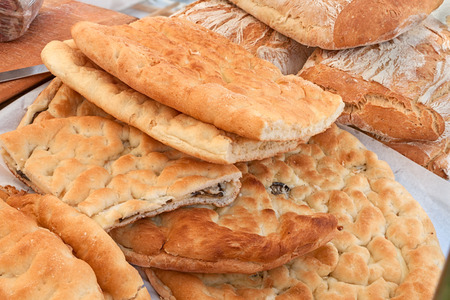 ovenbaked: Italian food: traditional focaccia (schiacciata of Tuscany), a flat oven-baked bread product with olive oil, very popular in Italy. Similar to pizza doughs but more soft and thick, can be stuffed with vegetables or meat Stock Photo
