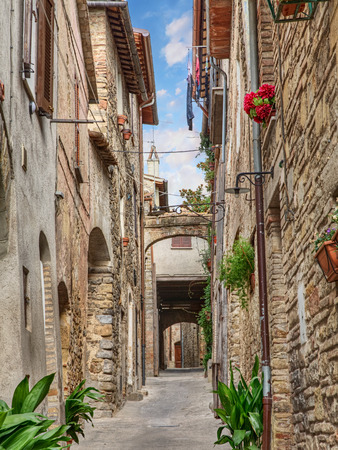 bevagna: picturesque narrow alley with ancient building, arch, underpass, plants and flowers in Bevagna, Umbria, Italy