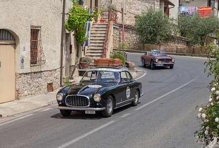 c a w: the crew W. Roell C. Roell on a rare vintage car Ferrari 212 Inter Coup? Pinin Farina (1953) travels in Tuscan village during the historic race Mille Miglia, on May 17, 2014 in Colle di Val d Elsa, Tuscany, Italy