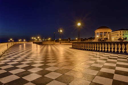 bannister: Mascagni Terrace at night, promenade of Livorno, Tuscany, Italy, an elegant square on the coast with black and white checkered floor, columned bannister and a round gazebo Stock Photo