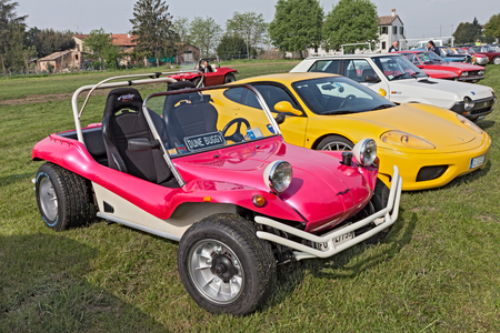 the seventies: vintage offroad car Volkswagen Dune Buggy of the seventies next to a Ferrari in classic cars rally 15th auto moto raduno on April 25 2015 in Piangipane RA Italy Editorial