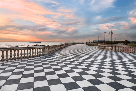 Mascagni Terrace promenade of Livorno Tuscany Italy  picturesque seashore at sunset with black and white checkered pavement and columned bannister