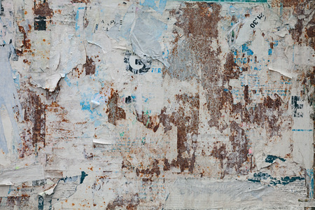 grunge ripped poster background - texture of torn advertisement on an old rusty billboard panel Foto de archivo