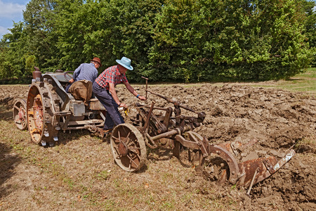 ploughing field: farmers recalling the old farm work plowing the field with an old tractor Landini hot bulb engine during the country fair  Sagra Paesana di Bastia  on May 17 2015 in Bastia RA Italy