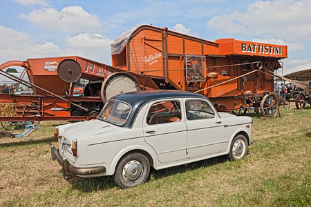 thresh: vintage car Fiat 1100 in the field near to an old wheat thresher in the country fair  Sagra Paesana di Bastia  on May 17 2015 in Bastia RA Italy Editorial