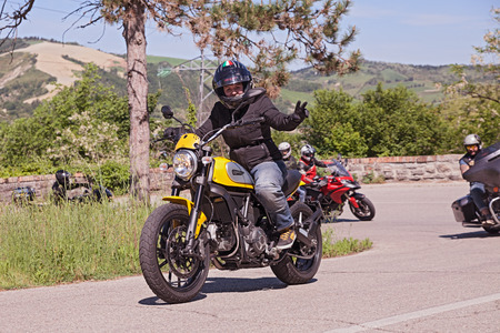 scrambler: Biker riding italian motorbike Ducati Scrambler with a group of bikers in motorcycle rally Mototagliatella on May 10 2015 in Predappio Italy