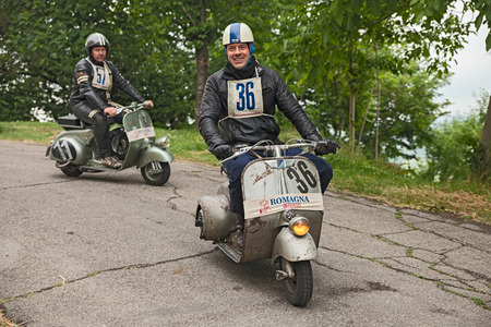 forties: biker riding a vintage italian scooter Vespa Piaggio in rally of classic Vespa of the forties - fifties Trofeo dellappennino on May 16, 2015 in Teodorano, FC, Italy