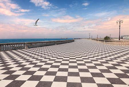 cuadros blanco y negro: Mascagni Terraza en la madrugada, el paseo marítimo de Livorno, Toscana, Italia - pintoresca orilla del mar en el mar de Liguria con pavimento a cuadros blanco y negro y la barandilla de columnas