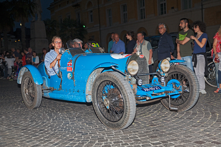 italian car: drivers on ancient Italian car Bugatti  T 37  1926 traveling at night in italian historic race for classic cars Mille Miglia on May 14, 2015 in Ravenna, Italy Editorial