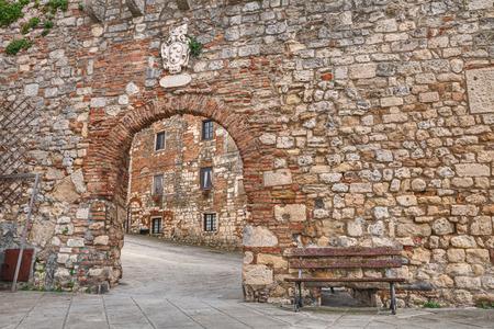 中世の村ロジニャーノ ・ マリッティモ、リボルノ、トスカーナ、イタリアの入り口の門の古代の石壁