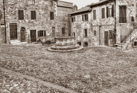 well: ancient square with water well in the italian old town Castiglione dOrcia, Tuscany, Italy - black and white image in sepia tone