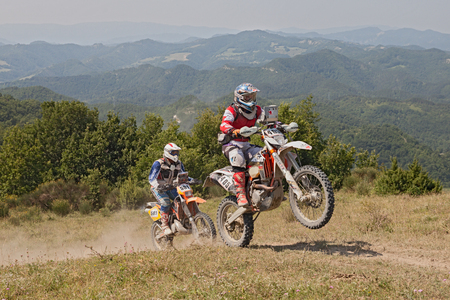 scrambler: bikers riding enduro motorcycles KTM 510 and KTM EXC 250 in the green mountains during the Italian championship Motorally Terre di Romagna, on July 5, 2015 in Predappio, FC, Italy Editorial