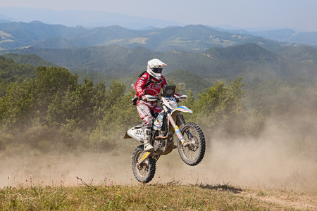 scrambler: biker riding enduro motorcycles Husqvarna FE 350 in the green mountains during the Italian championship Motorally Terre di Romagna, on July 5, 2015 in Predappio, FC, Italy