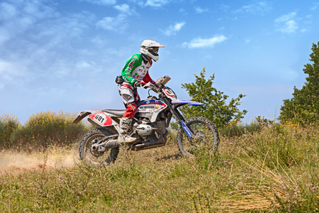 scrambler: biker riding enduro motorcycle Bmw GS 1200 RR in the green mountains during the Italian championship Motorally Terre di Romagna, on July 5, 2015 in Predappio, FC, Italy