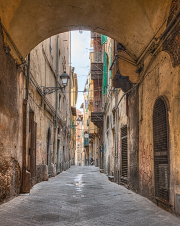 arches: picturesque ancient italian alley with arch and ancient houses - typical narrow street in the old town of Pisa, Tuscany, Italy
