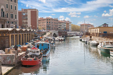 characteristic: picturesque view of the characteristic old port canal with fishing boats in the Italian town Leghorn, on April 14, 2015 in the city Livorno, Tuscany, Italy Editorial