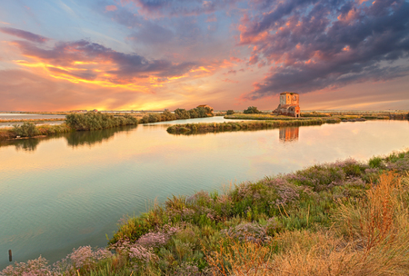 emilia romagna: landscape at sunset of the swamp with ruins of an old house - the lagoon in the natural reserve of Comacchio, Ferrara, Italy