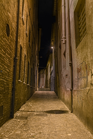 urban decline: narrow dark alley in the old town - ancient distressed alleyway in the italian city - grunge aged street at night
