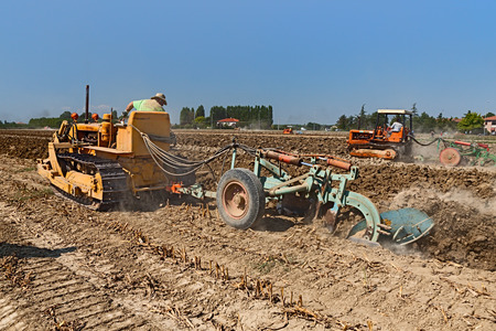 crawler: farmer plowing the field with an old crawler tractor Fiat and the plow during the country fair Rombi agricoli on August 30, 2015 in SantAgata sul Santerno, Ravenna, Italy Editorial