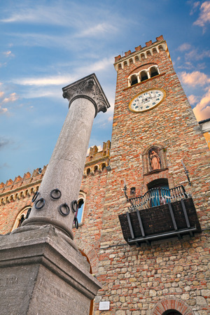 emilia romagna: the ancient Column of hospitality in Bertinoro, Emilia Romagna, Italy, with the rings for tying the horses and the medieval clock tower of the Communal Palace in background Stock Photo