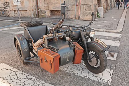 reenact: old BMW R75 750 cc, World War II-era German motorcycle with sidecar, armed with a machine gun, at the military vehicle rally during the festival Fiera di San Rocco on November 2, 2014 in Faenza, Italy