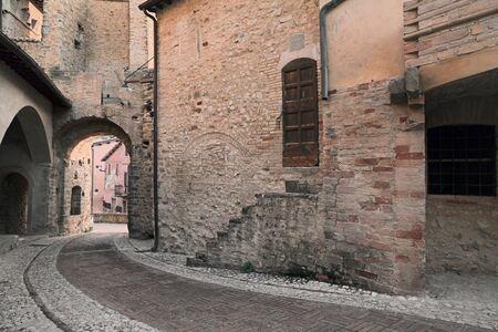 古代コーナーとレンガとウンブリア州、イタリアの中世の村の旧市街の石畳舗装された路地 写真素材
