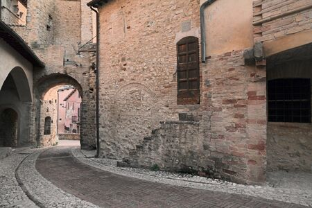 ancient corner and alley paved with brick and cobblestone in the old town of a medieval village in Umbria, Italy